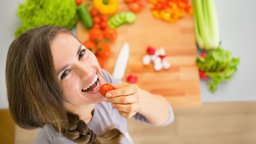 Mujer joven comiendo un tomate y cocinando vegetales