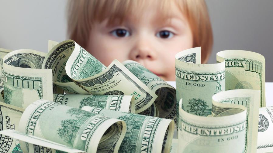 Niña pequeña asomándose detrás de billetes de dólar