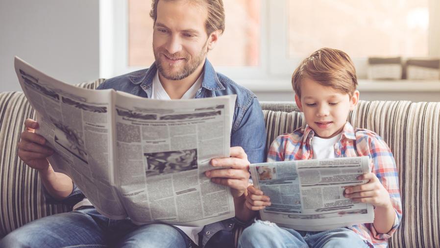 Padre e hijo leyendo periódicos en el sofá