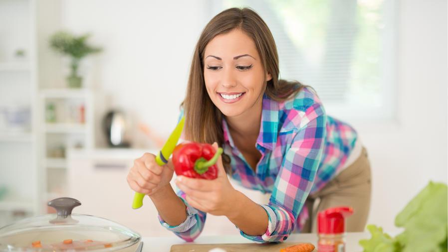 Mujer con un pimiento en la cocina