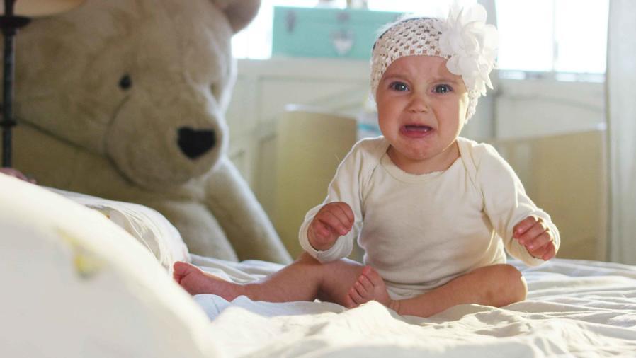 Bebé llorando sentada en la cama