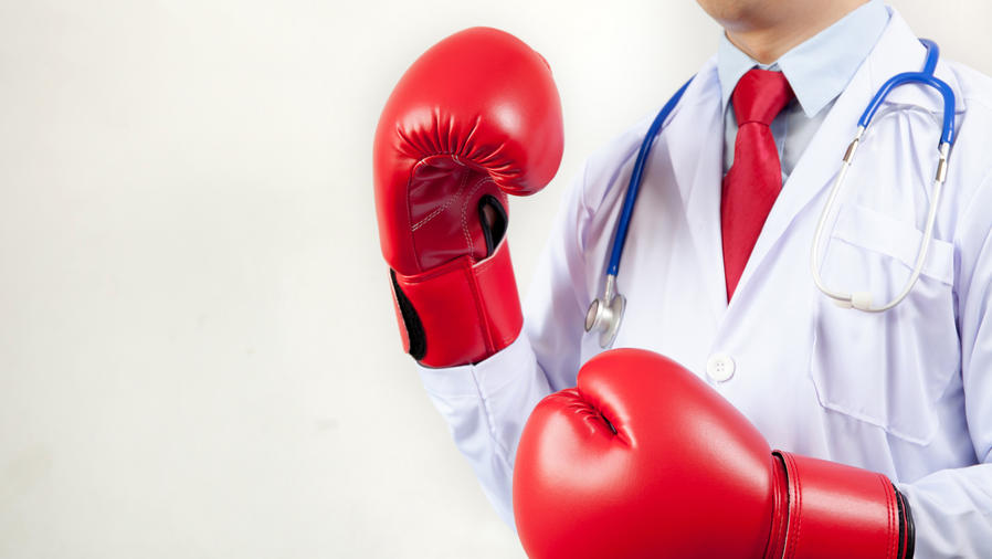 Médico con bata blanca y guantes de boxeo