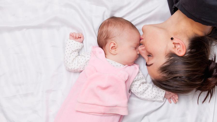 Madre besando a bebé pequeña en la frente