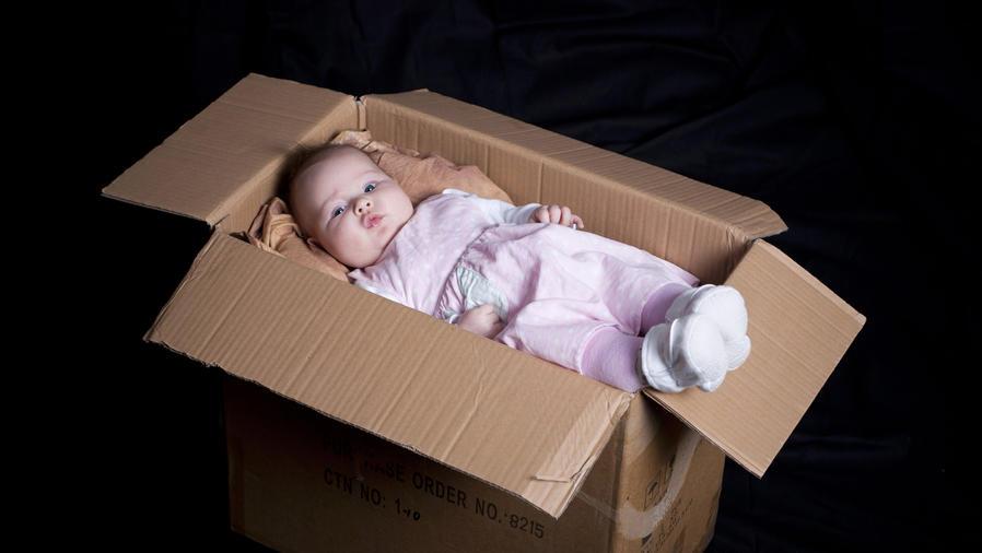Bebé acostado en una caja de cartón