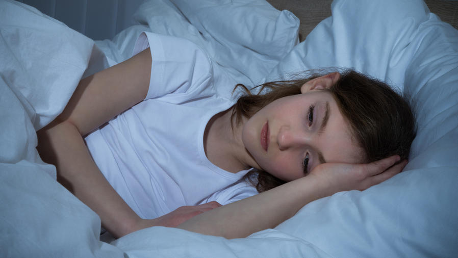 Niña acostada con problemas para dormir