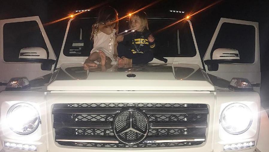 Penelope y Reign Disick sentados sobre un auto