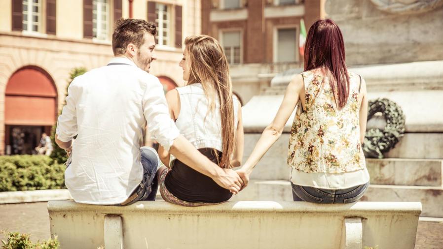 Hombre tomando la mano de una mujer mientras está sentado con otra
