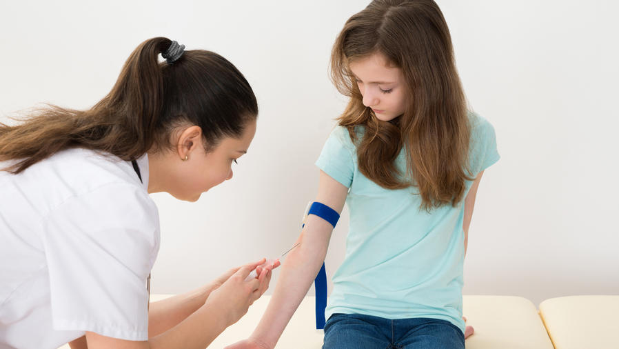 Doctor toma muestra de sangre de niña