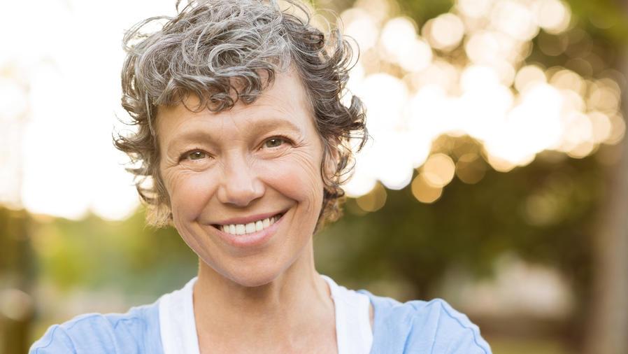 Mujer de cabello gris sonriendo