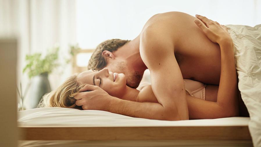 Pareja en la cama desnudos y abrazados