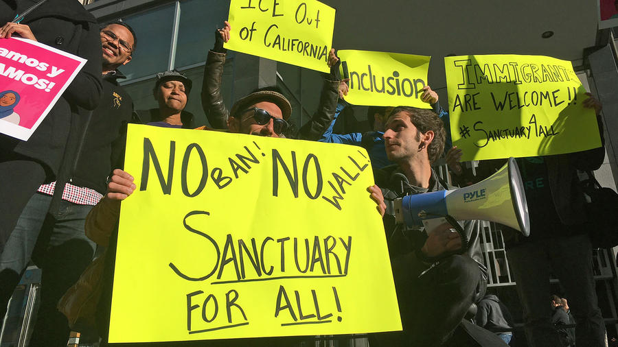 Manifestantes sostienen letreros a las afueras de una corte en la que un juez federal escuchará argumentos en la primera demanda que disputa el decreto del presidente Trump para retener fondos a las comunidades que limiten su cooperación con inmigración