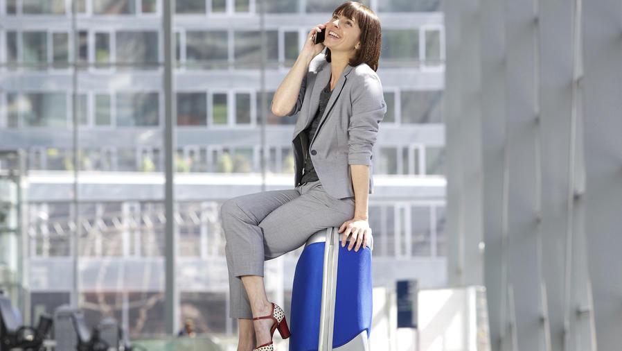 Mujer sentada sobre valija