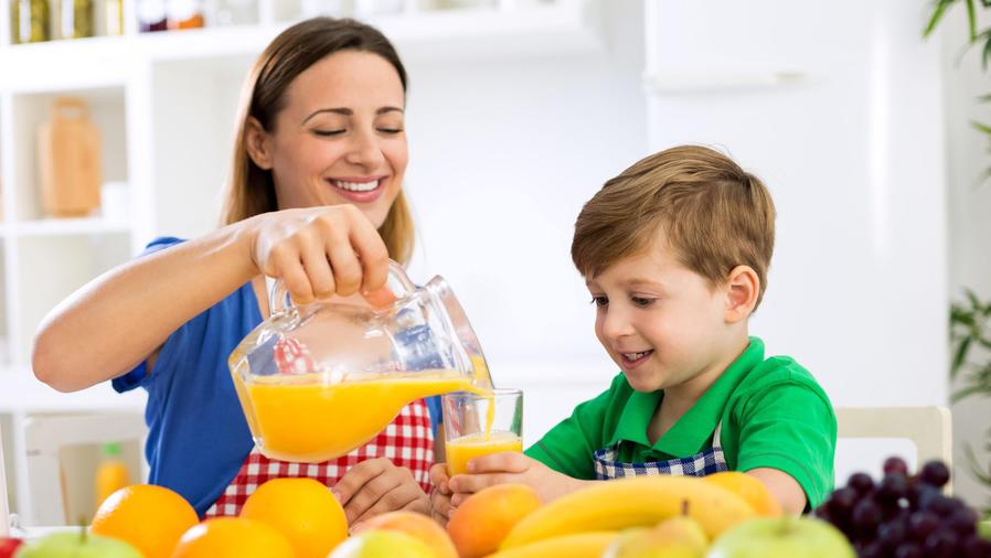 Madre sirviendo jugo de naranja a su hijo