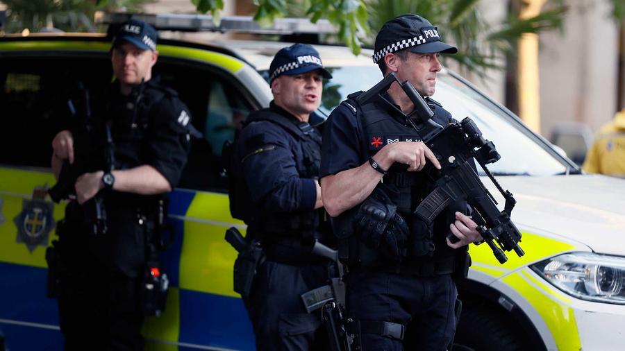 Policías cuidan a los asistentes a la vigilia por las víctimas del ataque suicida en el concierto de Ariana Grande