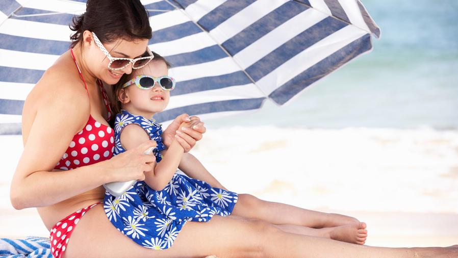 Madre e hija en la playa bajo una sombrilla, aplicándose protector solar