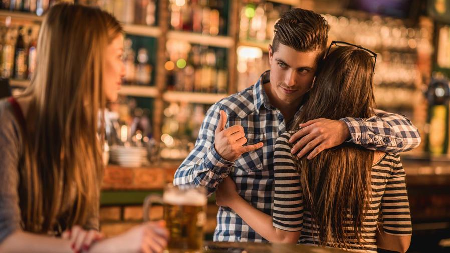 Hombre haciendo señas a otra chica mientras abraza a su novia