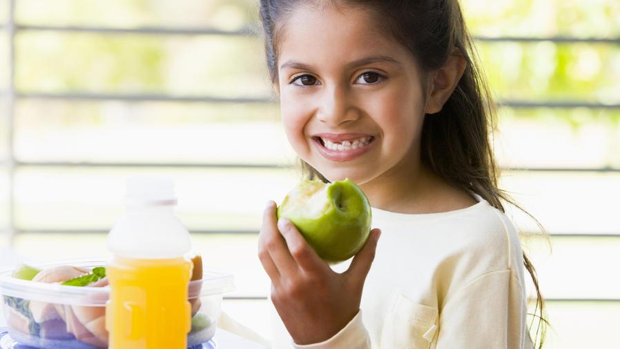 Niña hispana comiendo saludable