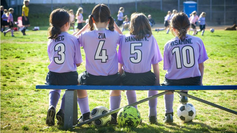 Equipo de niñas de fúbtol sentadas a la orilla del campo