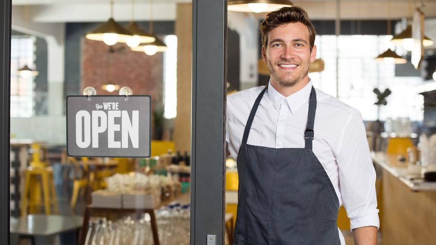 Joven en la puerta de su negocio