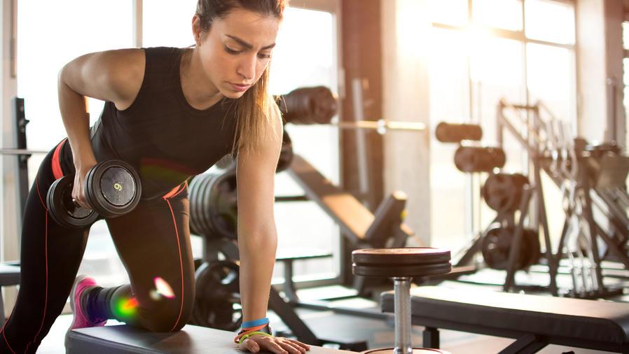 Mujer joven haciendo ejercicio con mancuernas