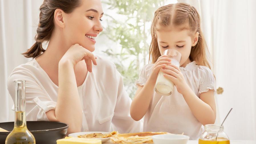 Madre e hija desayunando leche