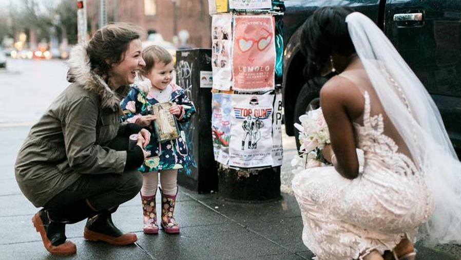 Mujer vestida de novia platicando con una niña y su madre