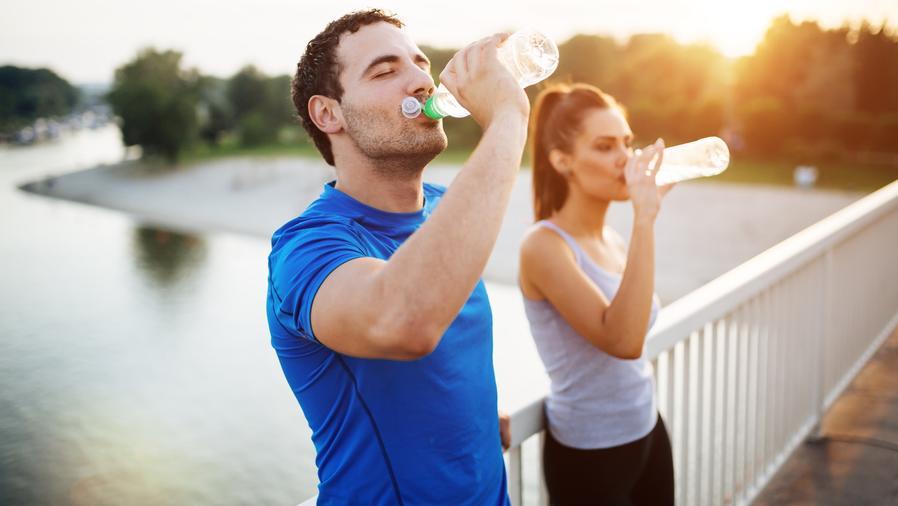 Hombre y mujer bebiendo agua al aire libre
