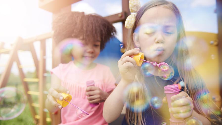 Niñas jugando con burbujas en el parque