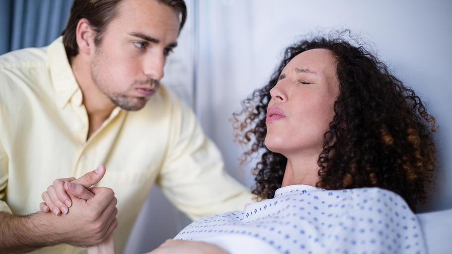 Hombre sostiene mano de mujer embarazada