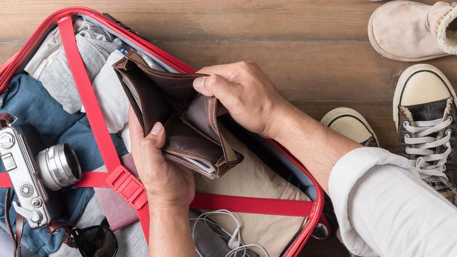 Hombre con valija y billetera vacía