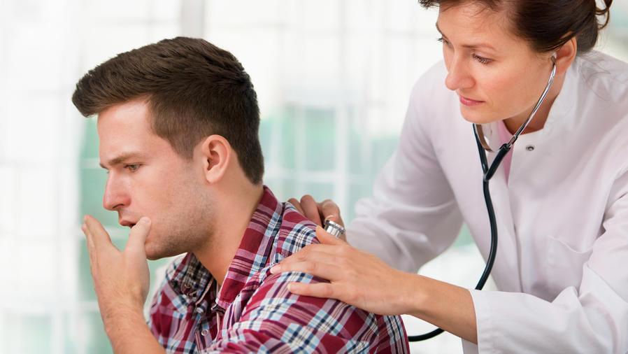 Hombre tosiendo en un control médico
