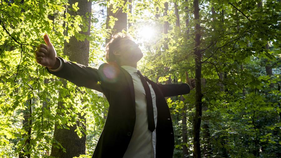 Hombre en traje con los brazos abiertos en el bosque