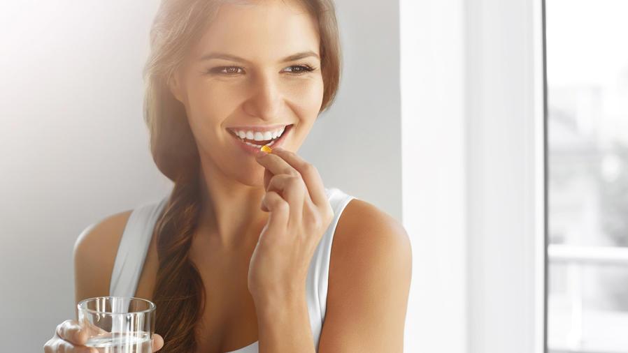 Mujer sonriendo tomando una vitamina con un vaso de agua