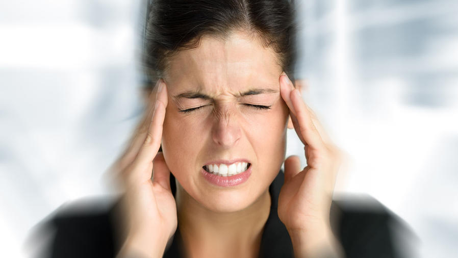 Mujer con dolor de cabeza tocándose la sien
