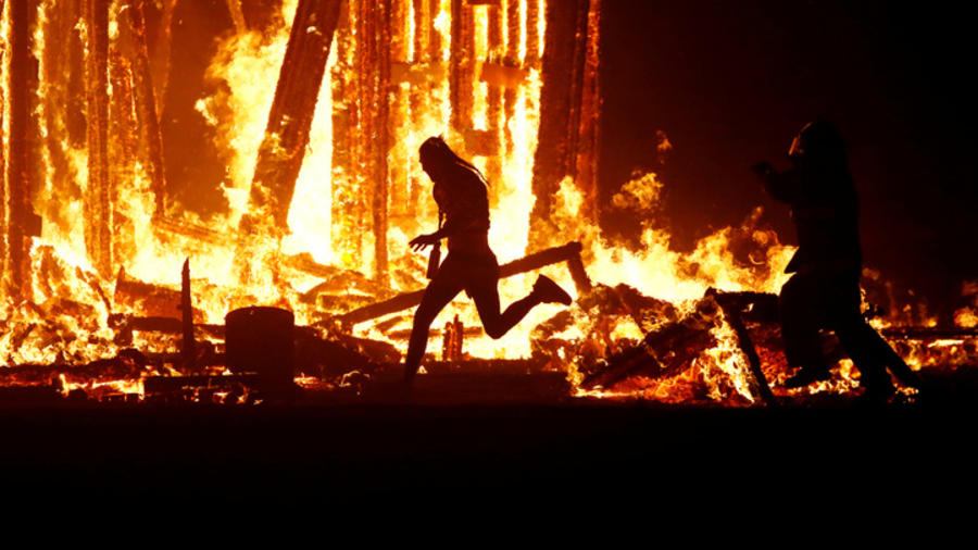 "Burning Man participant runs into the flames of the ""Man Burn"" at the Burning Man arts and music festival in the Black Rock Desert of Nevada"