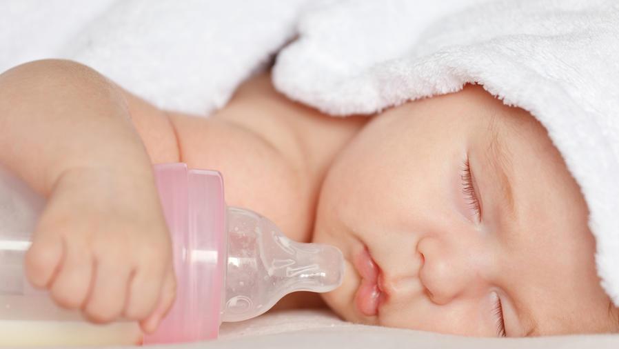 Bebé durmiendo con el biberón
