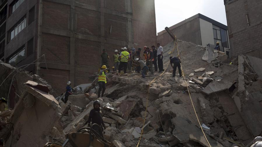 Personas trabajando en los escombros tras el sismo