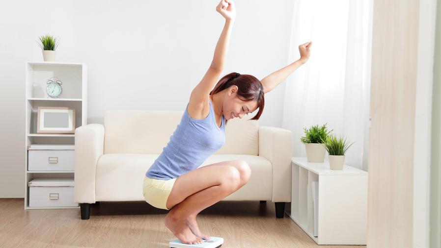 Mujer celebrando sobre la balanza