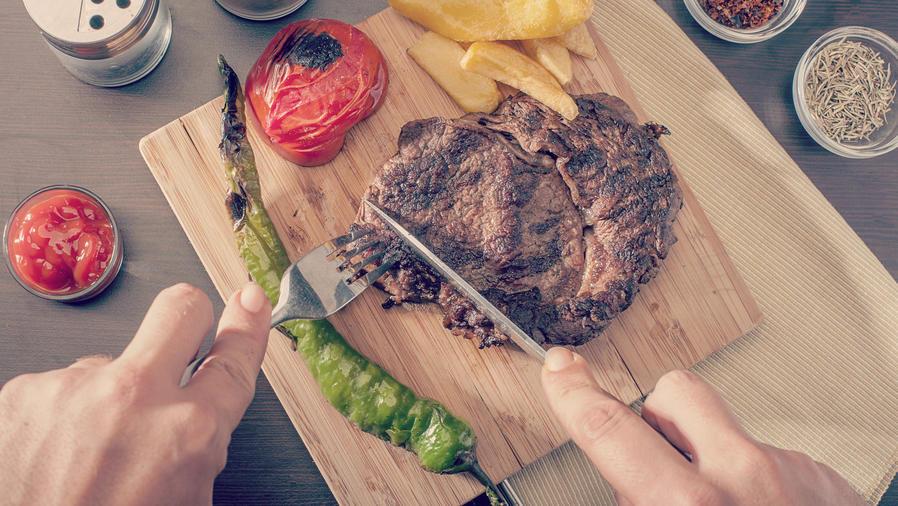 Hombre cortando un bife de carne roja