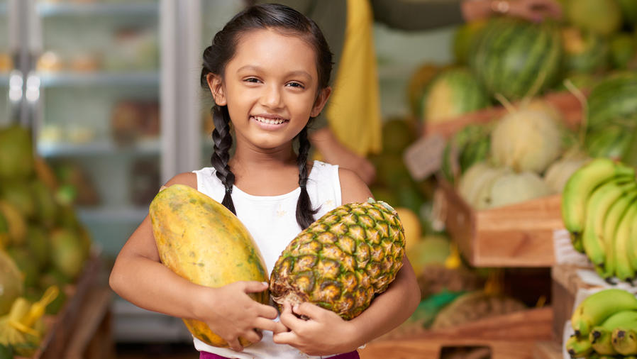 Niña sostiene frutas
