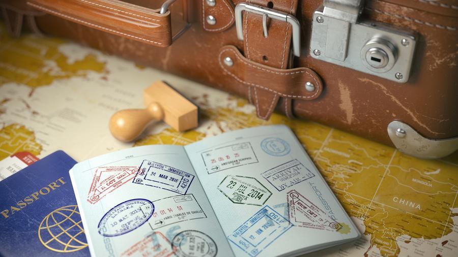 Pasaporte abierto junto a maleta y mapa