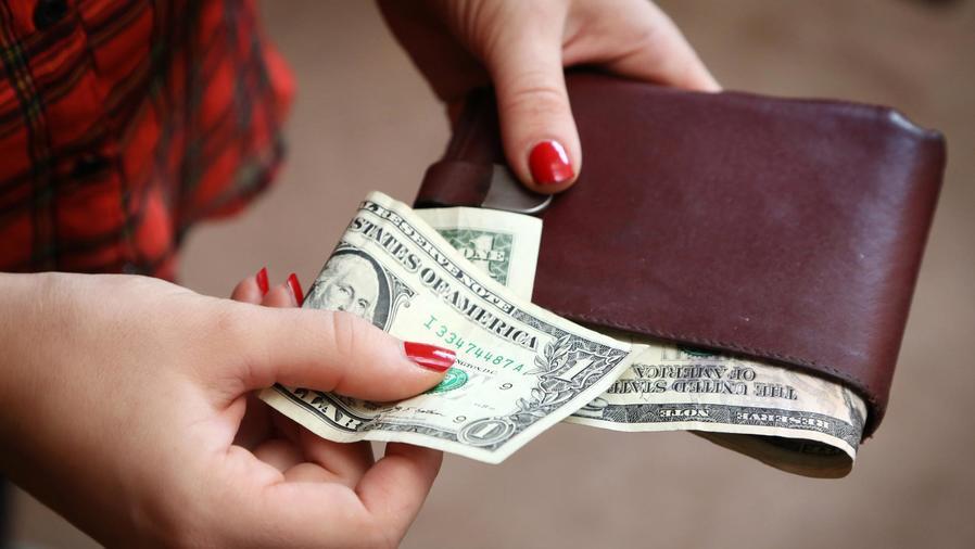 Mujer con una billetera y dólares en las manos