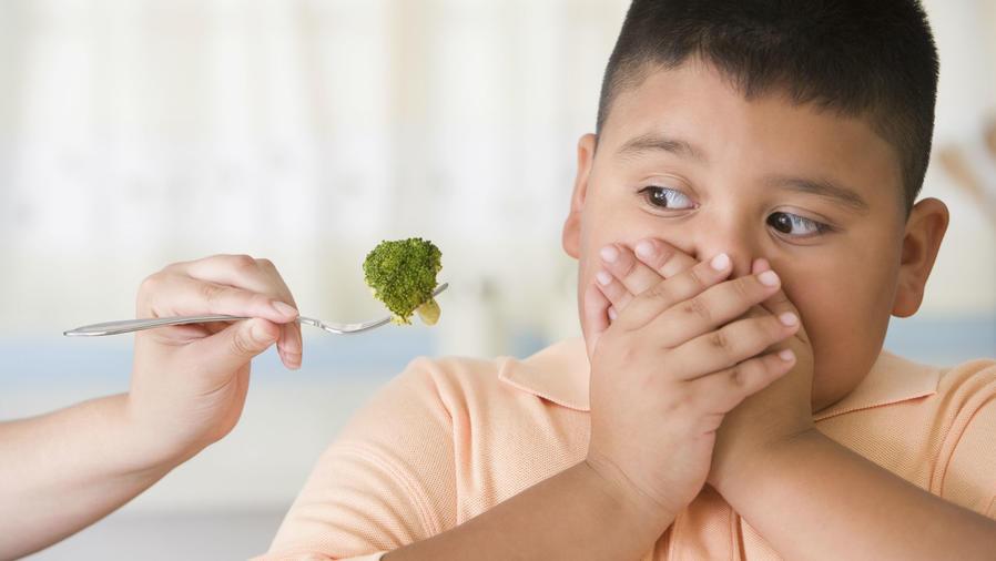 Niño con sobrepeso cubriéndose la boca