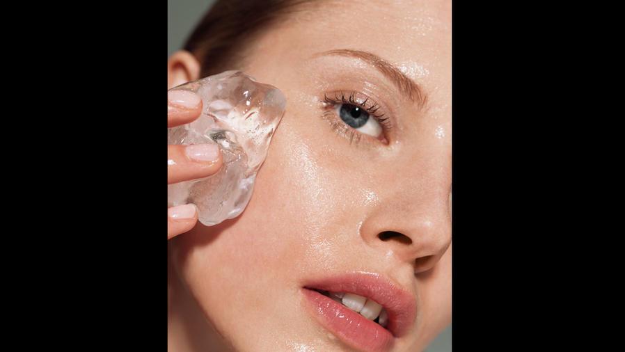 Mujer poniéndose hielo en la cara