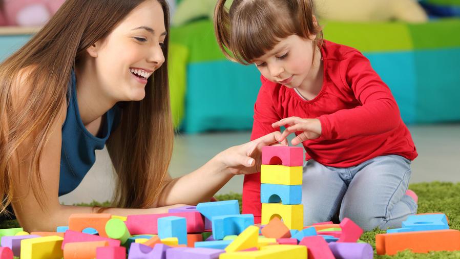 Madre e hija jugando con cubos de construccion