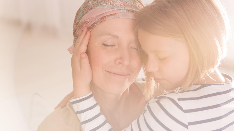 Niña abrazando a mujer con cáncer