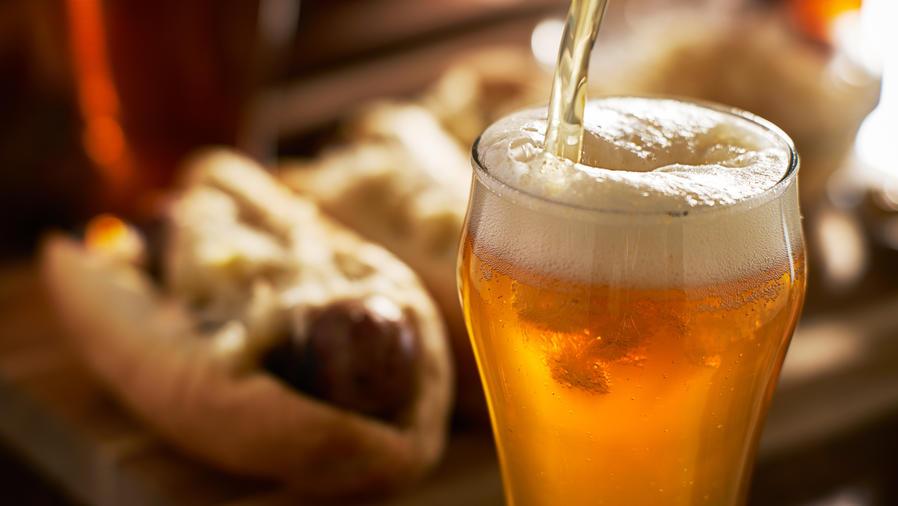 amber beer in mug with hotdog