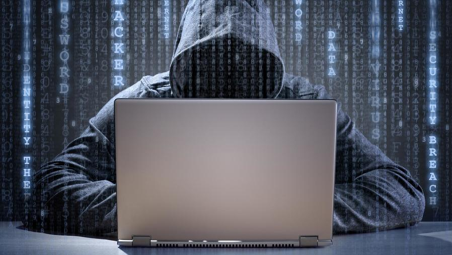 Hombre encapuchado usando computadora