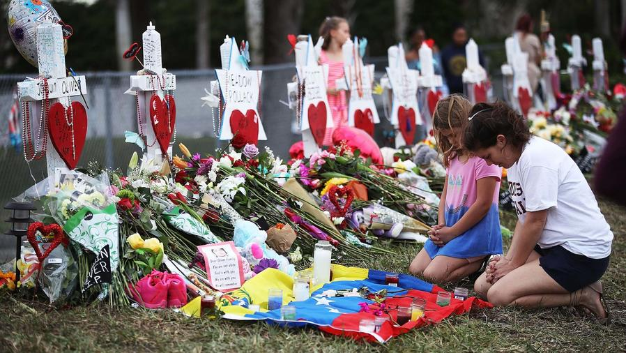 Mujer y niña frente a altares de víctimas