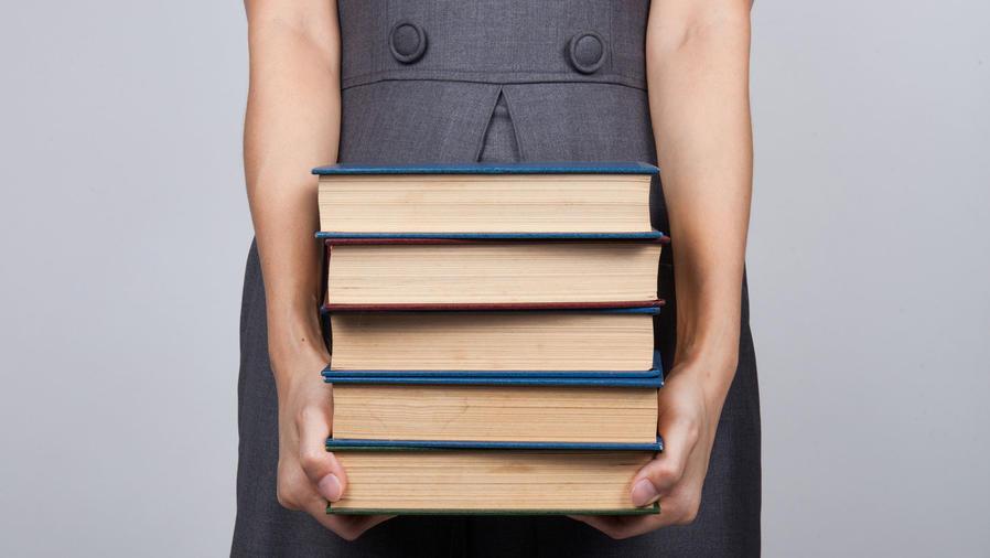 Mujer cargando una pila de libros